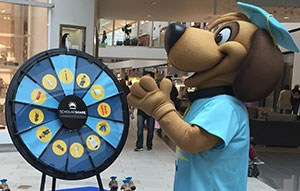 Scholarshare mascot spinning a prize wheel
